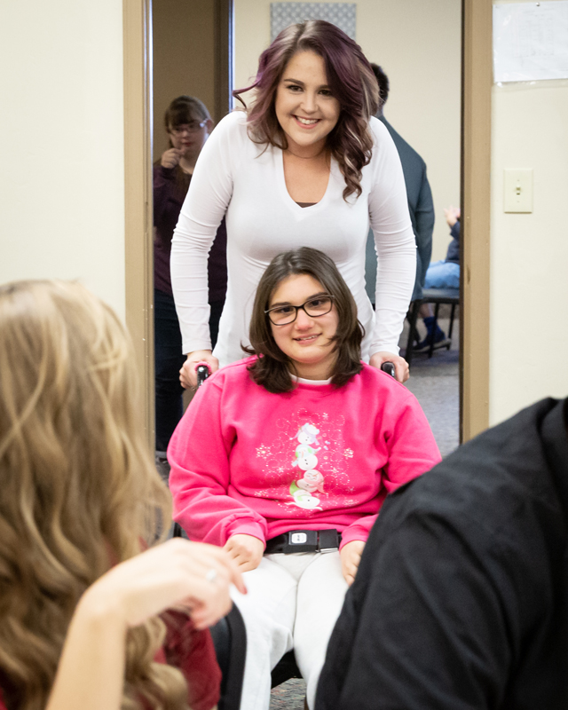Ability member smiling in a wheelchair with staff member