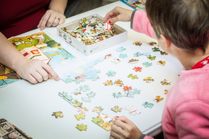 Child completing a puzzle with the help of an adult