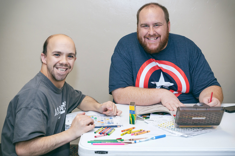 Two male Ability members working on an art project