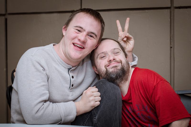 Two ability members smiling, one throwing the peace sign