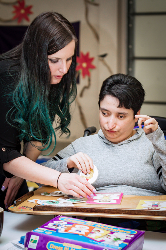 Ability member and staff member playing a board game