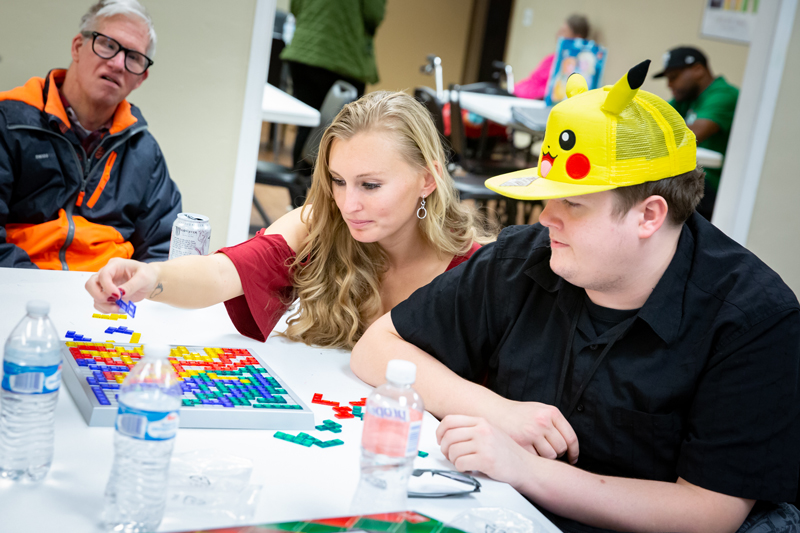Ability staff member playing a board game with an Ability member