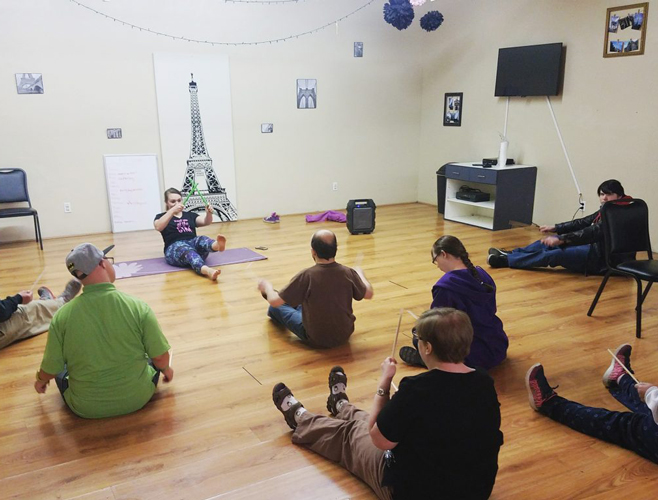 Ability members learning Yoga with an instructor