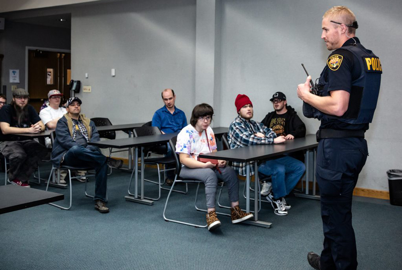 Group of Ability members listening to a speech from a police officer